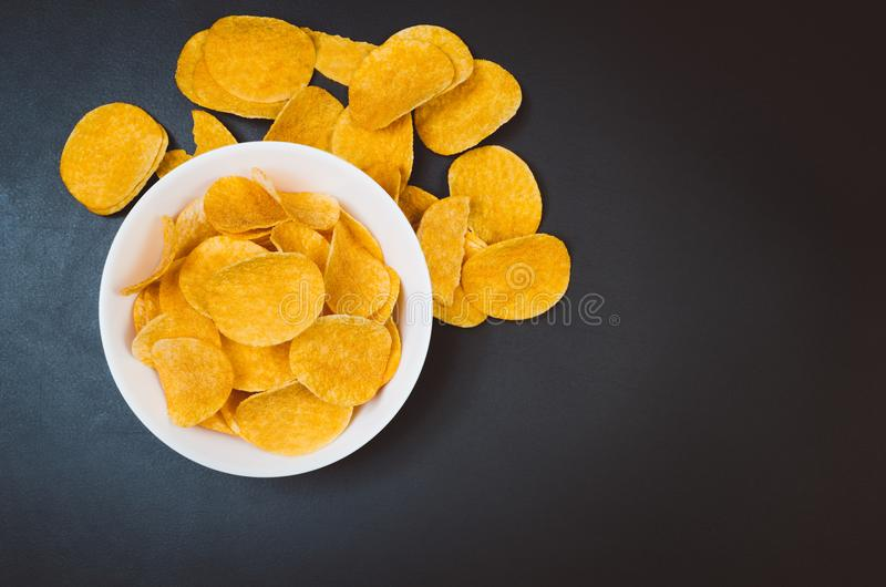 Potato chips and snacks on black slate table, top view royalty free stock photos