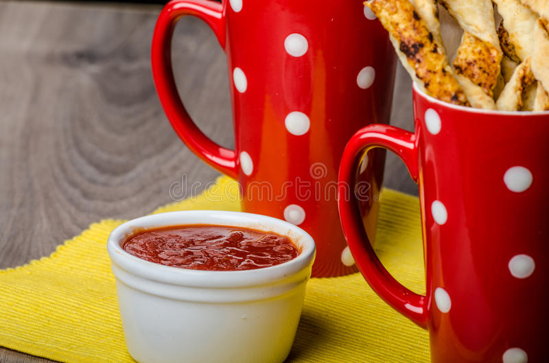 Party sticks from puff pastry. With hot sauce stock image