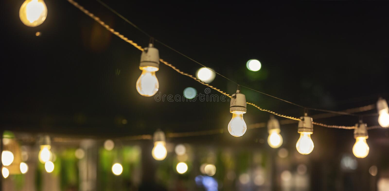 Party string lights hanging over outdoor restaurant terrace. At night stock photos
