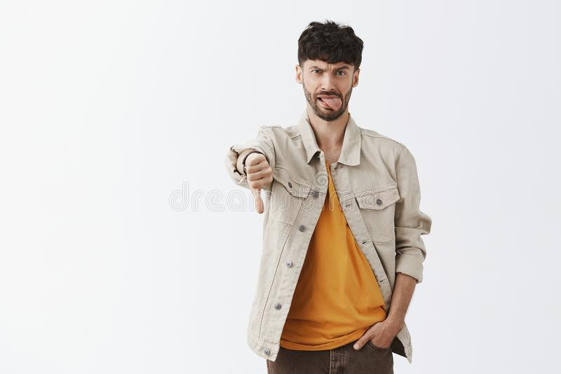 This party sucks, dislike. Displeased childish and emotive handsome modern male with beard in shirt over yellow t-shirt. Holding hand in pocket, showing thumb royalty free stock image