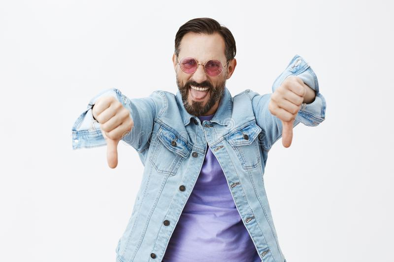 Party sucks, go home. Rebellious excited man being displeased and unimpressed, standing in sunglasses and denim jacket. Showing thumbs down and sticking tongue royalty free stock photo