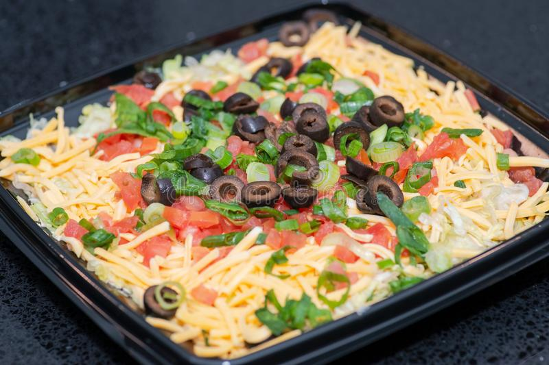 Party Taco Layer Dip. Zesty cream cheese and sour cream topped with lettuce, diced tomatoes, sliced olives, green onions stock photography