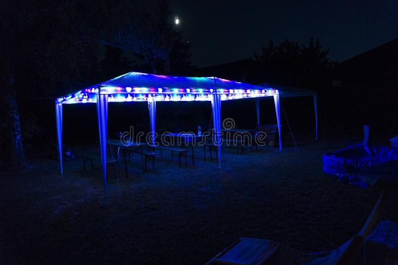 A party tent in the garden at night. In summer stock image