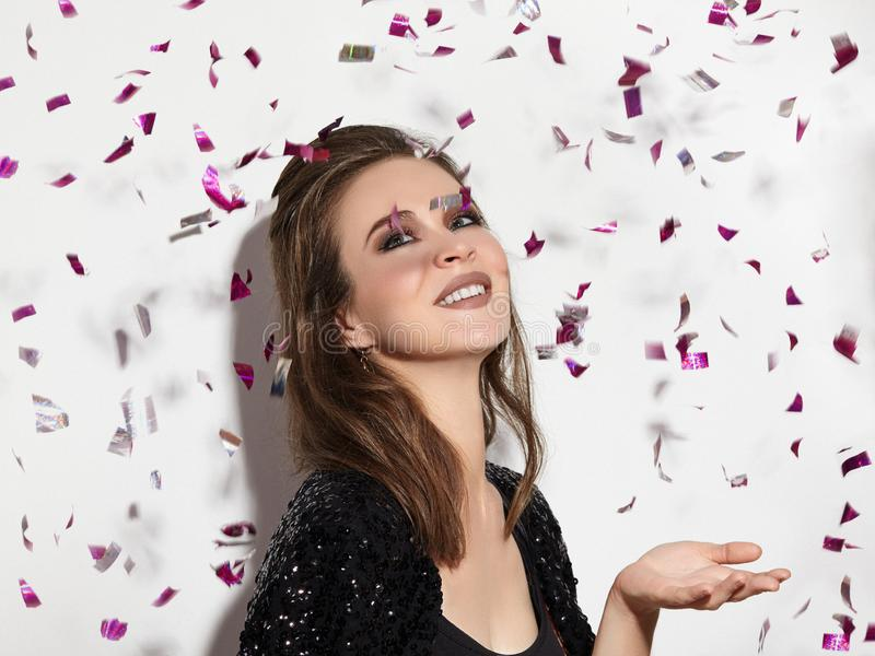 Party Time. Beautiful Happy Woman Smiling. Christmas Style in Confetti. Shiny Celebrate Look with Bright Fashion Make-up royalty free stock photography