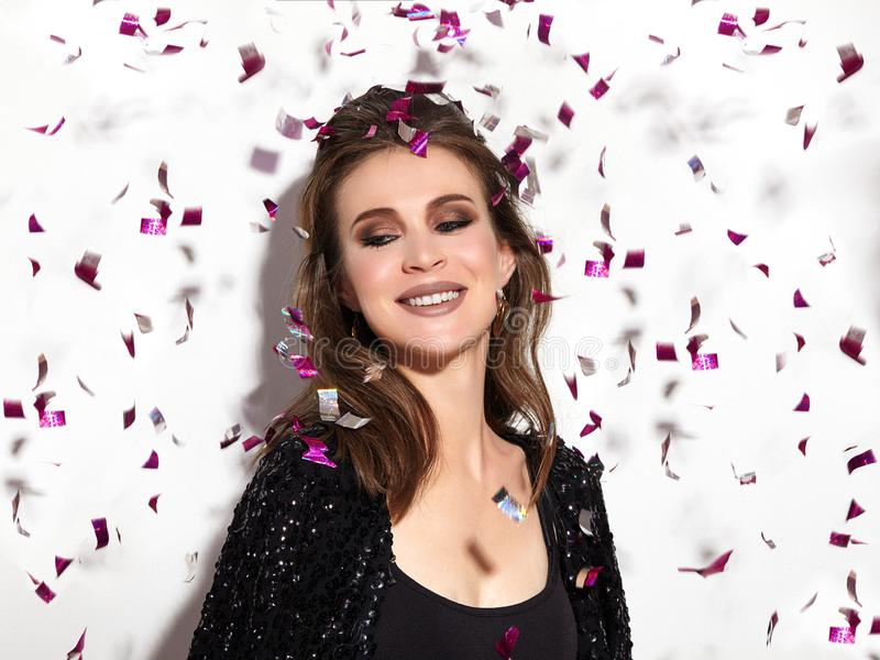 Party Time. Beautiful Happy Woman Smiling. Christmas Style in Confetti. Shiny Celebrate Look with Bright Fashion Make-up stock photo