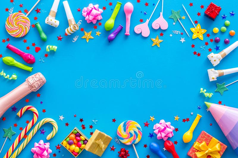 Party time frame with decorations on blue background top view mock up.  royalty free stock photo