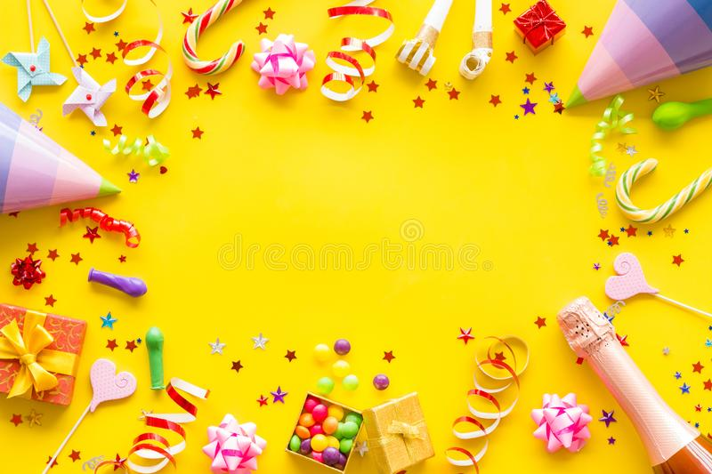 Party time frame with decorations on yellow background top view mock up.  royalty free stock image
