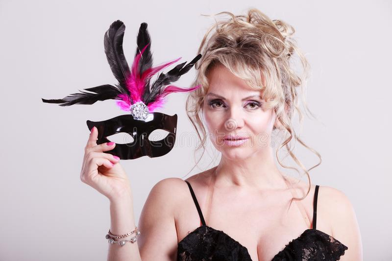 Woman middle aged holds carnival mask. stock image