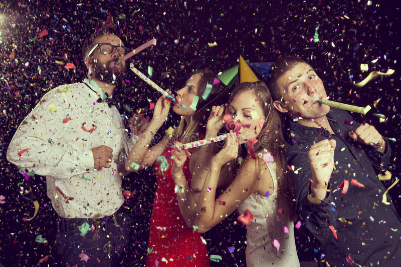 Party time. Two beautiful young couples having fun at New Year`s party, wearing party hats, dancing and blowing party whistles. Focus on the couple on the right royalty free stock photography