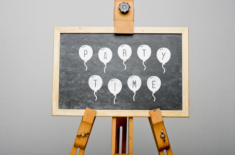 Party time written on balloons on black chalkboard, easel painting.  royalty free stock photo