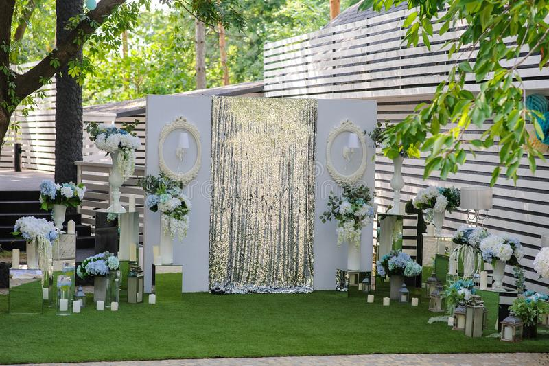 Party wedding decoration outdoor. Vintage metallic style, flowers decoration from: roses, hortensia and ranunculus. Vase from mirror. Candle on the floor stock image