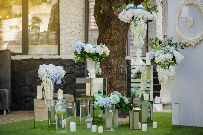 Party wedding decoration outdoor. Vintage metallic style, flowers decoration from: roses, hortensia and ranunculus. Vase from mirror. Candle on the floor stock photos