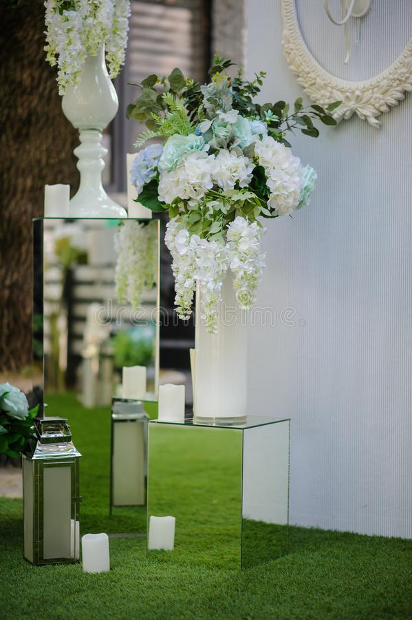 Party wedding decoration outdoor. Vintage metallic style, flowers decoration from: roses, hortensia and ranunculus. Vase from mirror. Candle on the floor stock photography