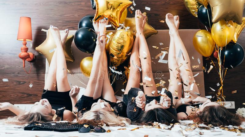 Party women joy fun confetti balloons legs. Party women. Fun and joy. Glitter confetti and balloons decor. Young females in black lying on bed legs up. Festive royalty free stock photography