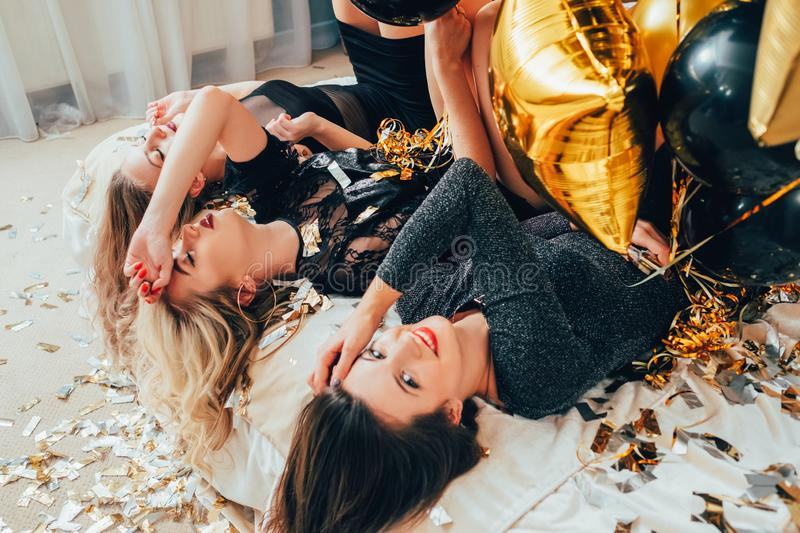 Party women relief relaxation confetti balloons. Party women upside down. Relief and relaxation. Females lying on bed. Eyes closed. Glitter confetti, balloons royalty free stock image