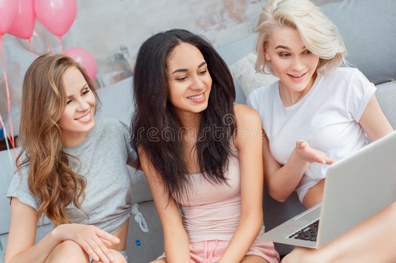 Party. Young women at home together sitting on floor browsing laptop smiling surprised close-up royalty free stock photo