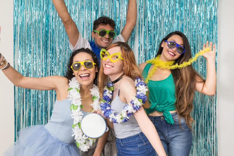 Partygoers are celebrating Carnival in Brazil. Caucasian woman h. Multi ethnic group of Brazilian friends. Costumed revelers are happy and celebrating the royalty free stock images