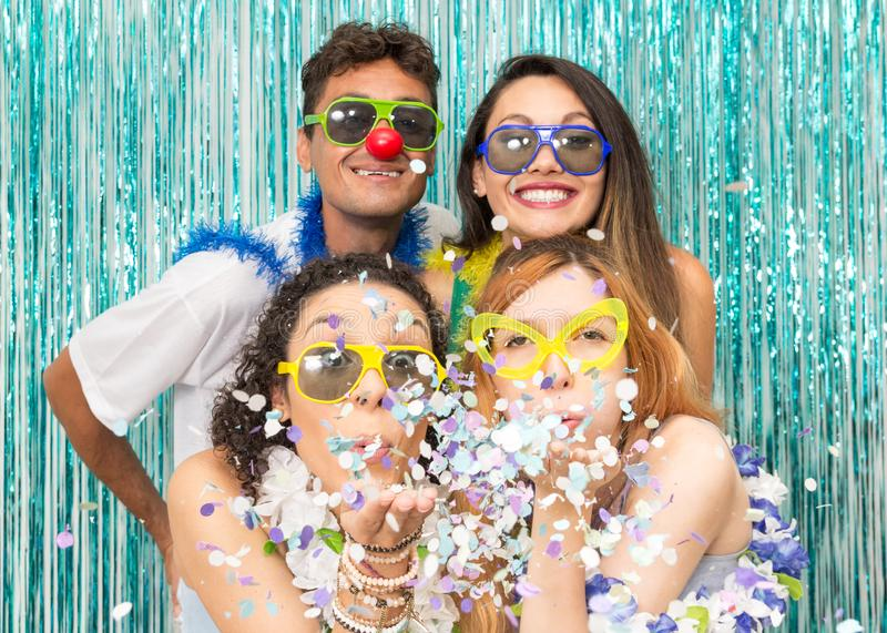 Partygoers are celebrating Carnival in Brazil. Girls blow the co. Multi ethnic group of Brazilian friends. Costumed revelers are happy and celebrating the stock image