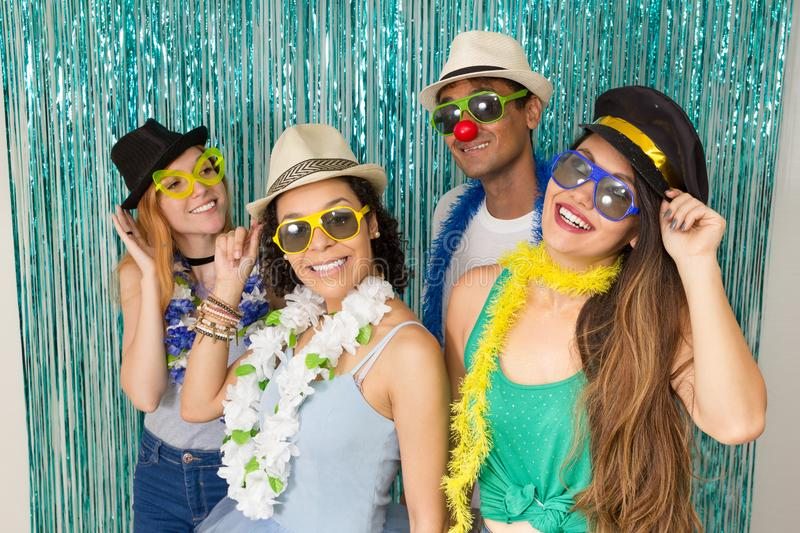 Partygoers are celebrating Carnival in Brazil. They wear sunglasses and hats.. Multi ethnic group of Brazilian friends. Costumed revelers are happy and royalty free stock photo