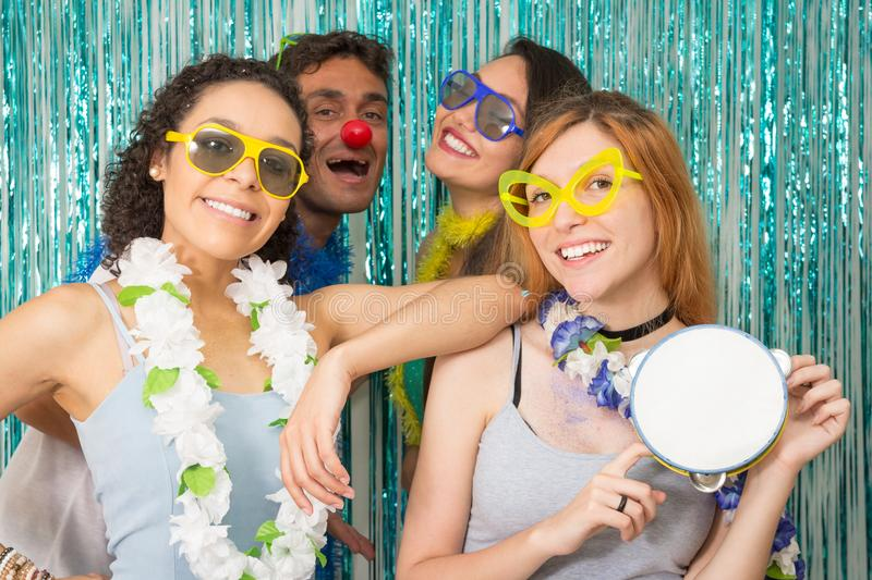 Partygoers are celebrating Carnival in Brazil. Woman holds a tam. Multi ethnic group of Brazilian friends. Costumed revelers are happy and celebrating the stock images