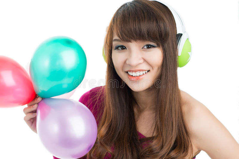 Partying teenager. Young pretty girl smiling at camera with balloons stock photo