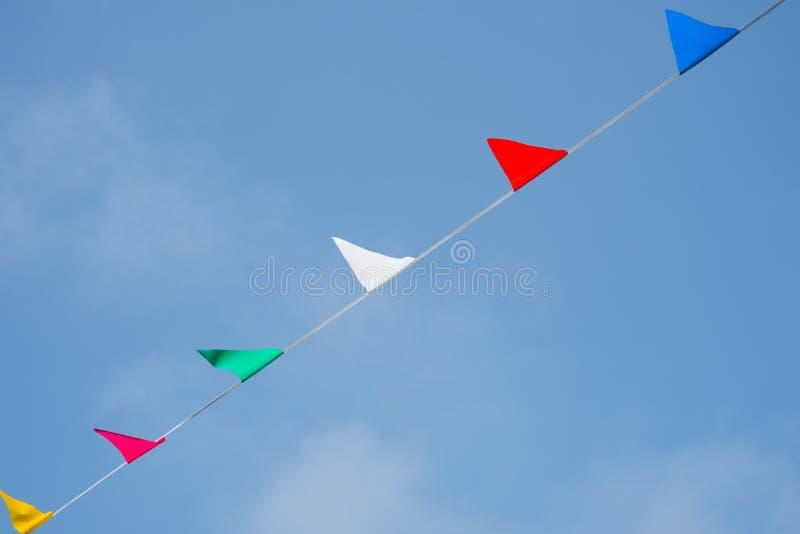 Partyjna dekoracja - kolorowe flaga wiesza na kreskowym aganst sk obrazy royalty free