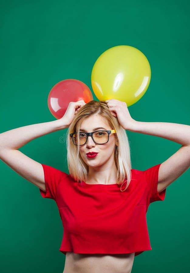 Partyjna dziewczyna w Modnych szkłach jest Grimacing i Przyglądająca Czerwoni Lotniczy balony w i zdjęcie royalty free