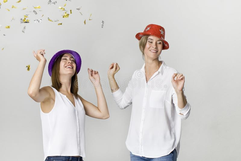 Partyjne dziewczyny z confetti i kolorowymi kapeluszami Ja jest relaxat zdjęcia stock