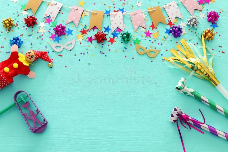 Partyjni kolorowi confetti z noisemaker nad lekkim pastelowym błękitnym drewnianym tłem Odgórny widok, mieszkanie nieatutowy zdjęcie stock