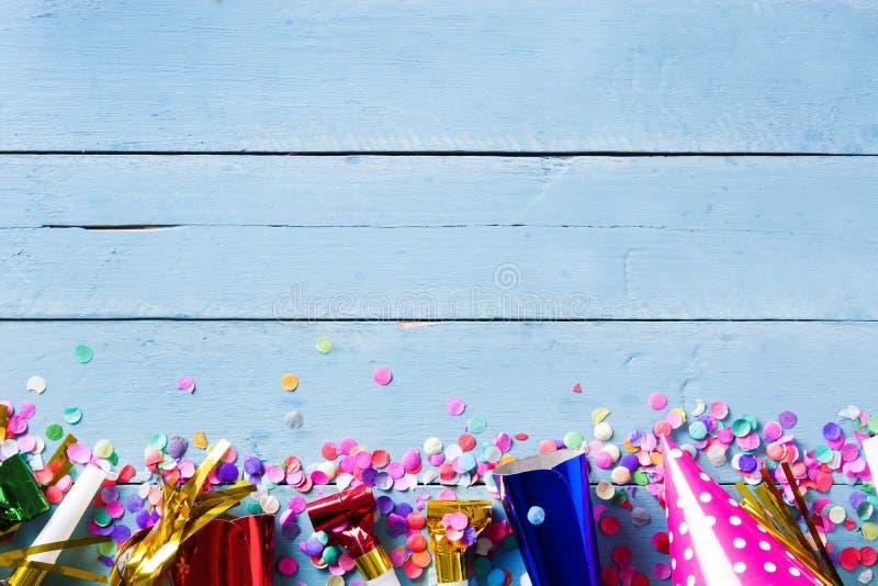 Partyjny tło Przyjęcie confetti na błękitnym drewnianym tle i nakrętki fotografia royalty free