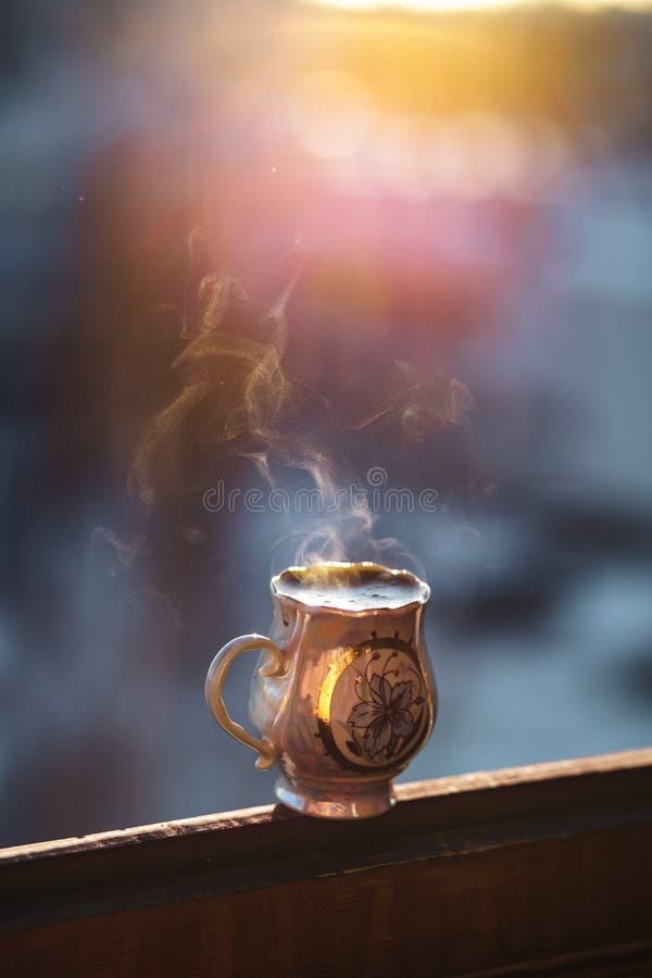 Parująca gorąca kawa w pięknie dekorującej porcelany filiżance zdjęcia stock