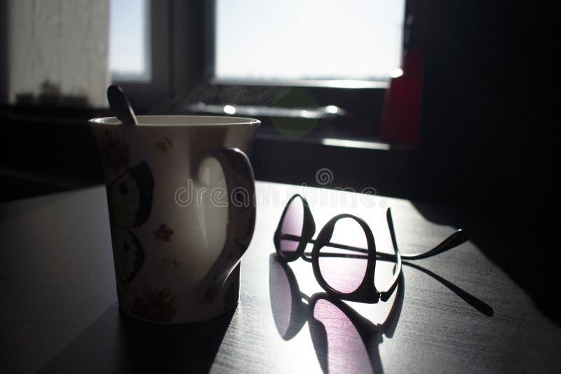 Parujący kawowy kubek z szkłami obraz stock