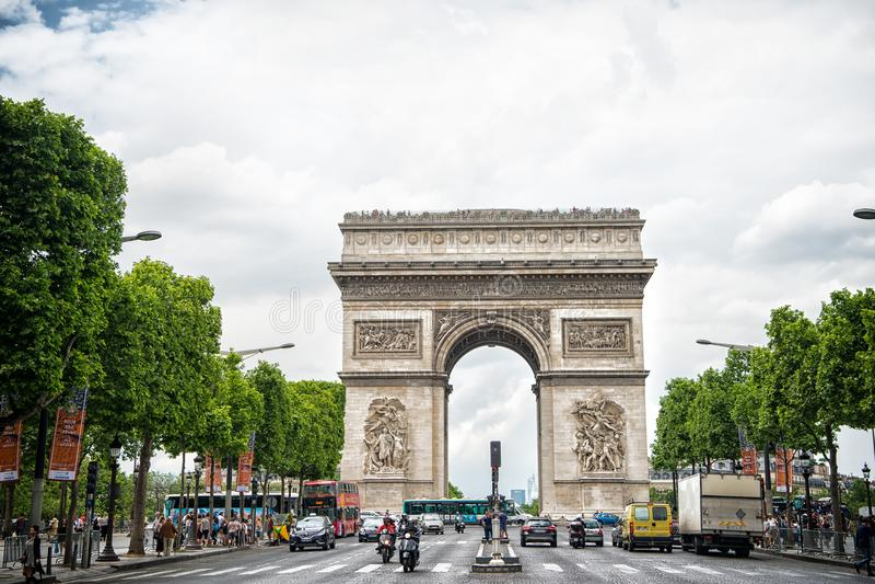 Paryż Francja, Czerwiec, - 02, 2017: Łękowaty zabytek w centre ruchliwie aleja Łuk De Triomphe na chmurnym niebie Wakacje i zwied zdjęcia royalty free