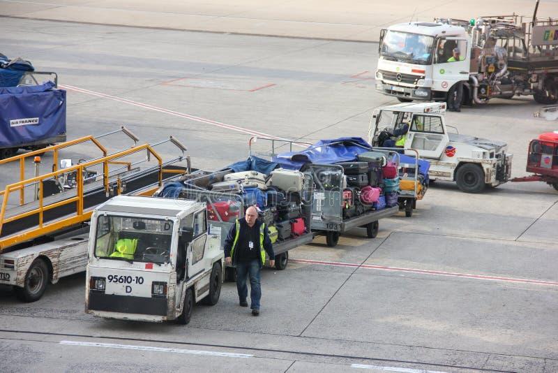 Paryż Francja, Kwiecień, - 2016: Pracownika sztaplowania bagaż na przyczepie od konwejeru na pasie startowym iść transportu samoc zdjęcia royalty free