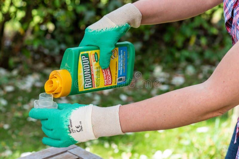 Paryż Francja, Sierpień, - 15, 2018: Ogrodniczka używa obława herbicyd w francuskim ogródzie Obława jest nazwą firmową herbicydu  obraz royalty free