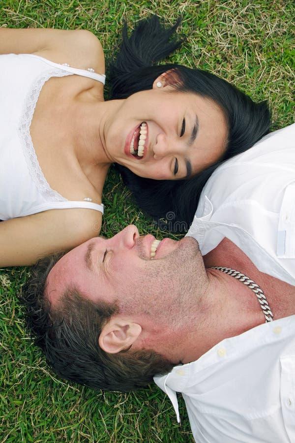 pary śmiechu gazonu lying on the beach zdjęcia royalty free