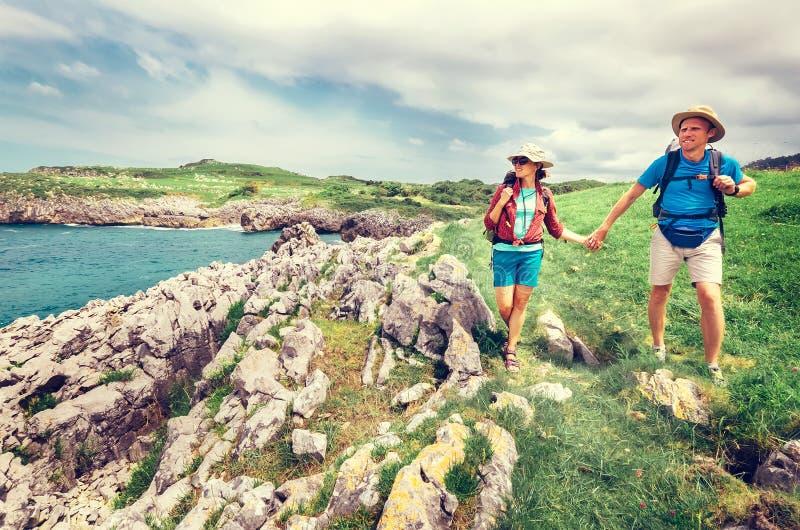Pary backpacker podr??nicy chodz? na oceanie skalisty brzegowy Asturias Hiszpania zdjęcie royalty free
