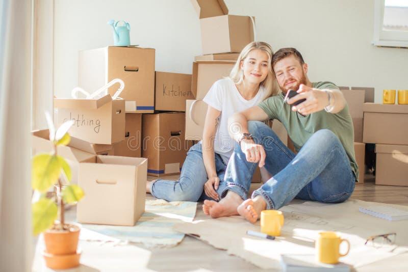 Pary chodzenie w nowym domu Siedzieć na podłogowym i relaksować po odpakowywać Robić selfie z smartphone zdjęcia stock