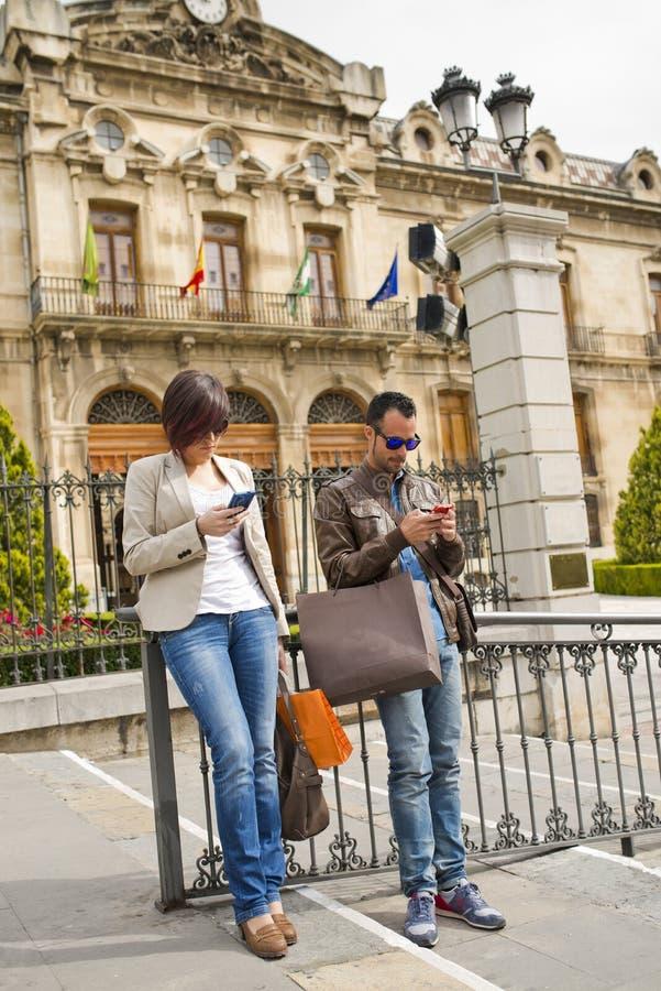 Pary dosłania sms przy outdoors miastem zdjęcie stock