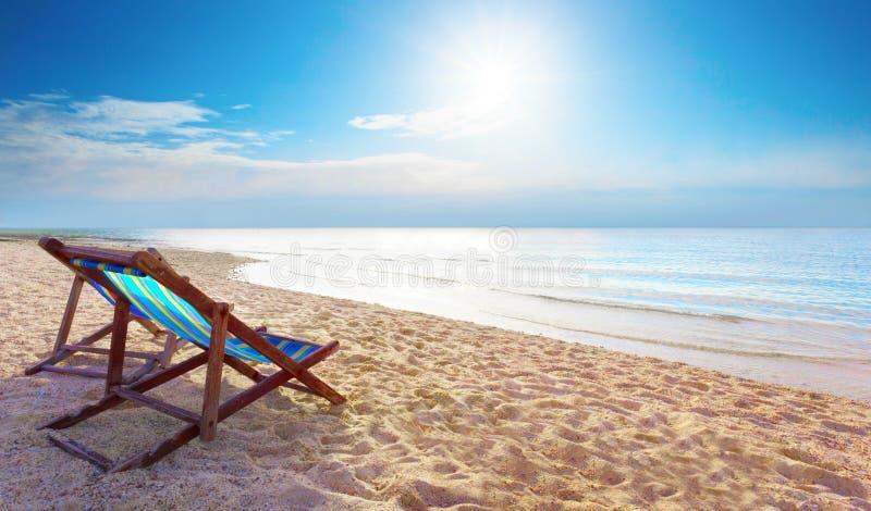 Pary drewniana krzesło plaża, niebieskie niebo przy denną stroną dla lata i obrazy royalty free