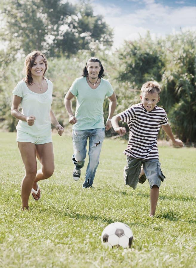 Pary i nastolatka chłopiec bawić się z piłki nożnej piłką zdjęcia royalty free