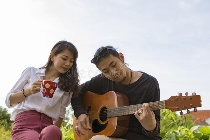 Pary młody mężczyzna, azjatykcia kobieta relaksuje i bawić się gitarę w parku zdjęcia stock