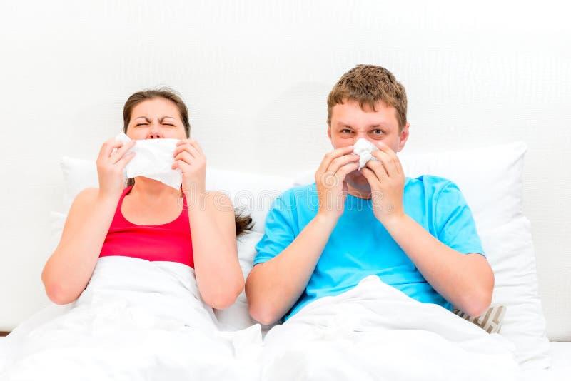 Pary małżeńskiej bolączka w łóżku i dmucha jej nos fotografia royalty free
