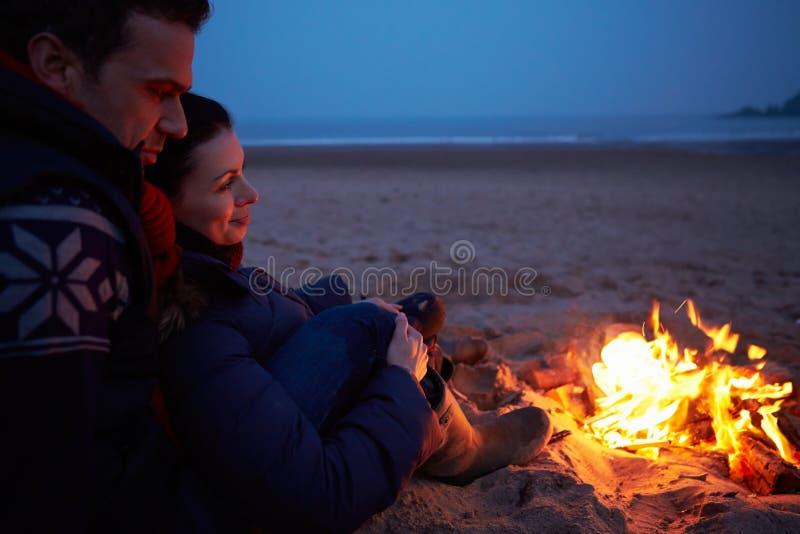 Pary obsiadanie ogieniem Na zimy plaży zdjęcie royalty free