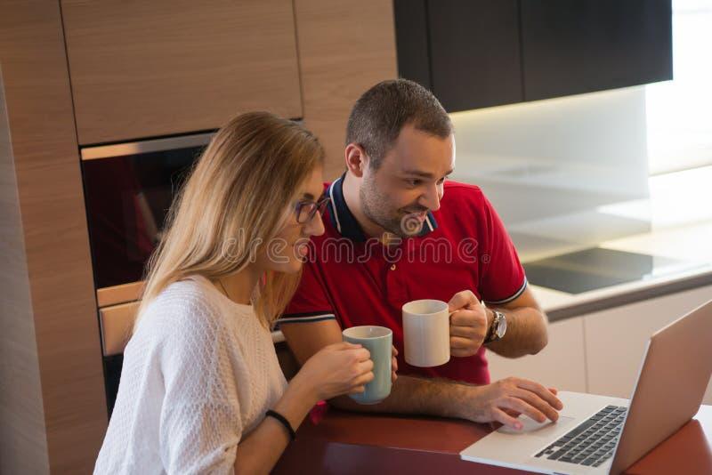 Pary pić kawowy w domu i używać laptop obrazy stock