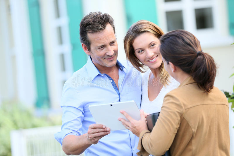 Pary spotkania agent nieruchomości przed ich nowym domem fotografia stock