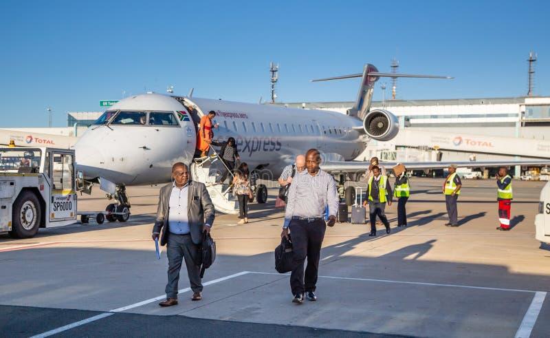 Pasażery zsiada od samolotu na asfalcie obraz stock