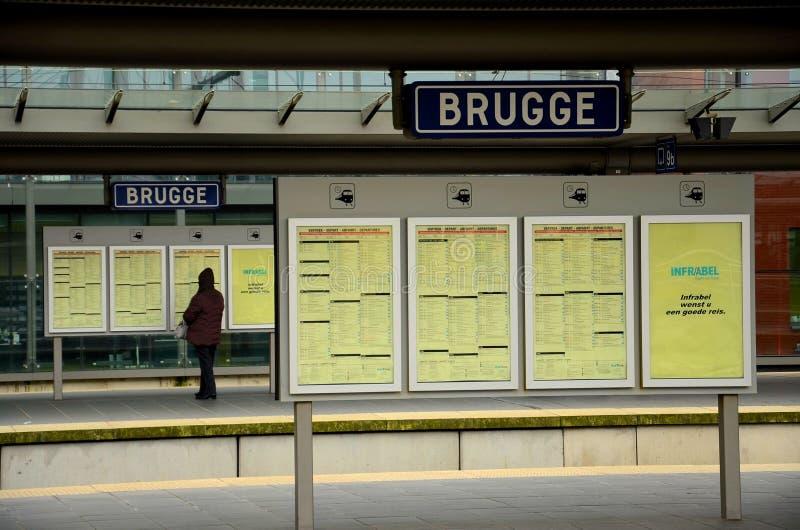 Pasażer czyta rozkład zajęć przy Brugge stacją kolejową, Belgia zdjęcie royalty free