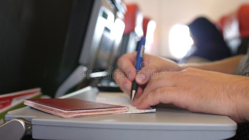 Pasażer z paszportem wypełnia w przesiedleńczych lub przyjazdowych kartach w samolocie podczas gdy lot zdjęcia royalty free
