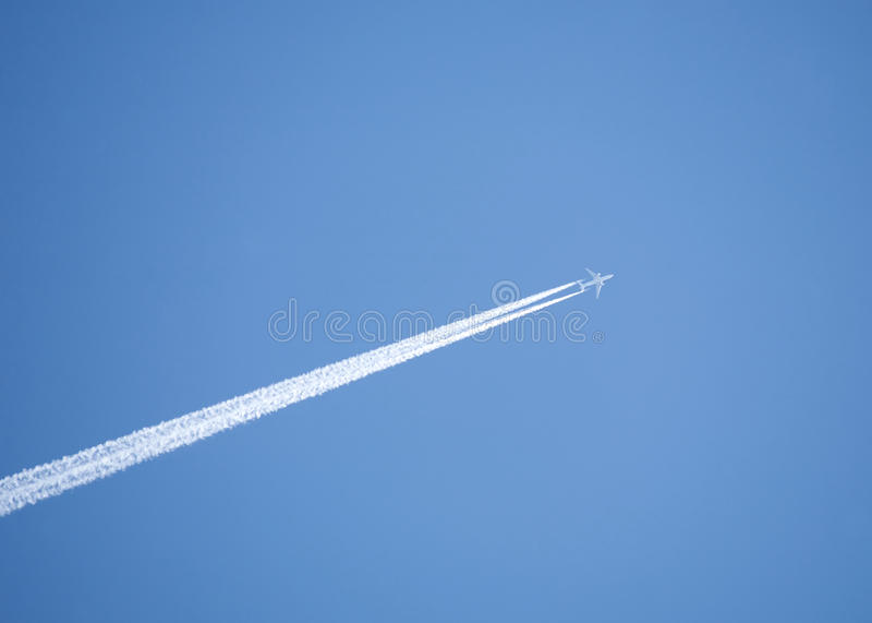 Pasażera samolotu odrzutowego latanie w jasnym niebieskim niebie, opuszcza białego ślad zdjęcie royalty free